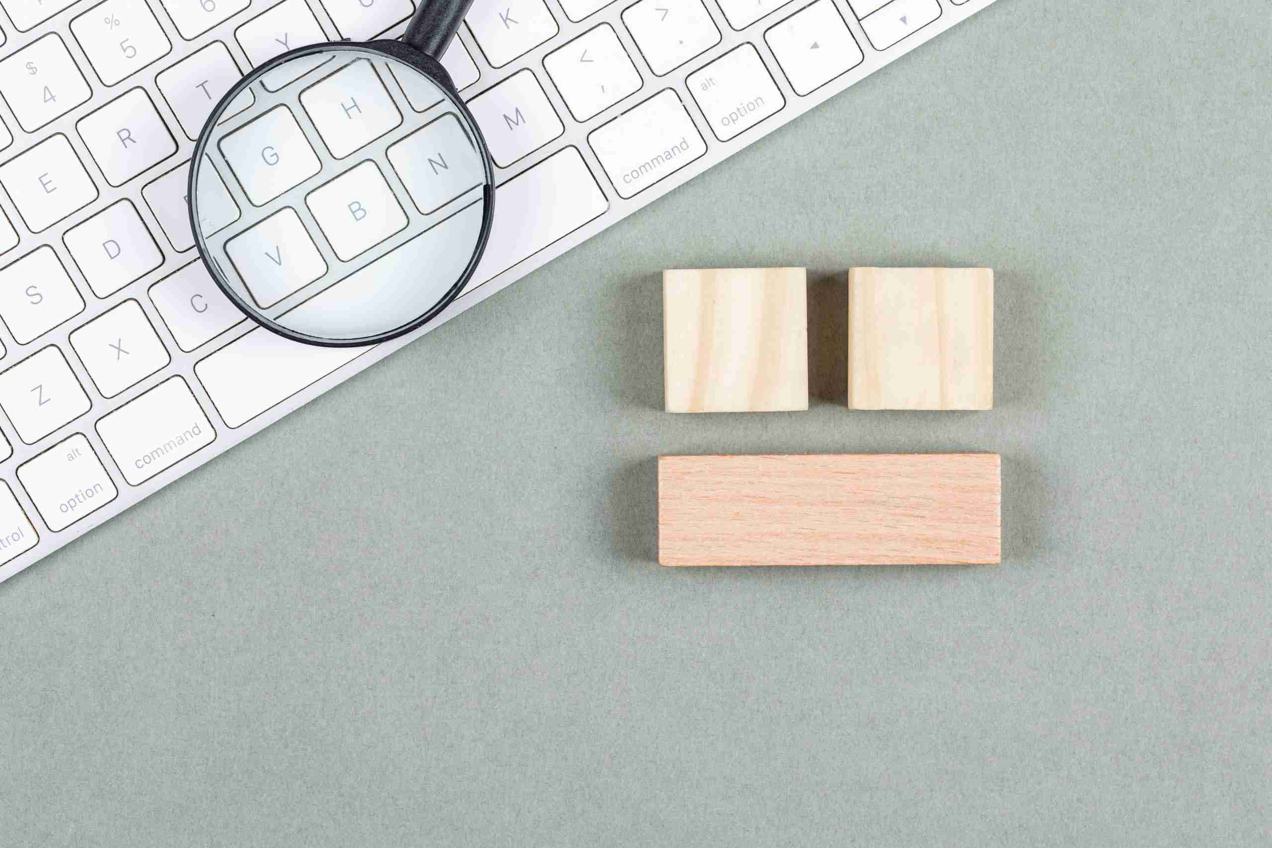 Search concept with magnifier, wooden blocks, keyboard on gray background top view. horizontal image